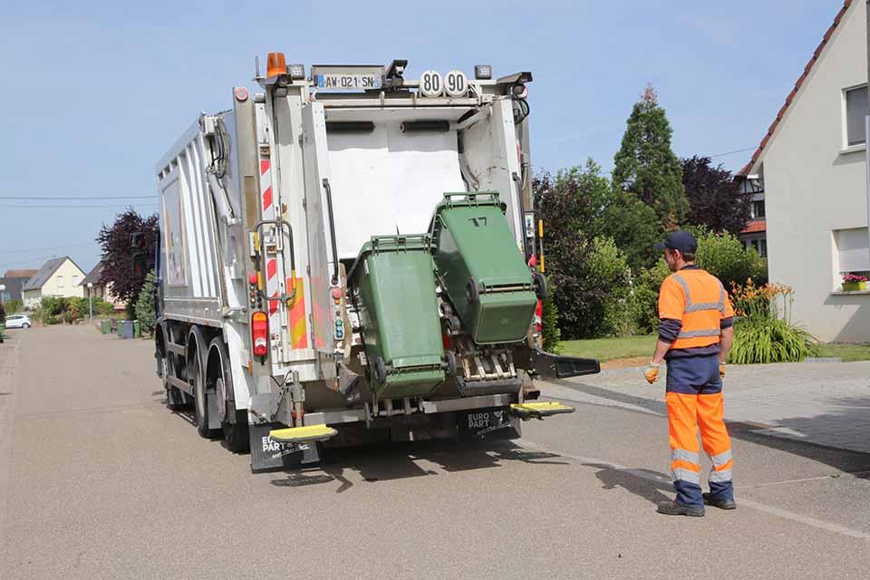 Camion vidant une poubelle verte